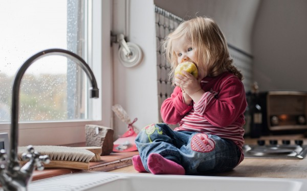 Toddler eating an apple in the kitchen